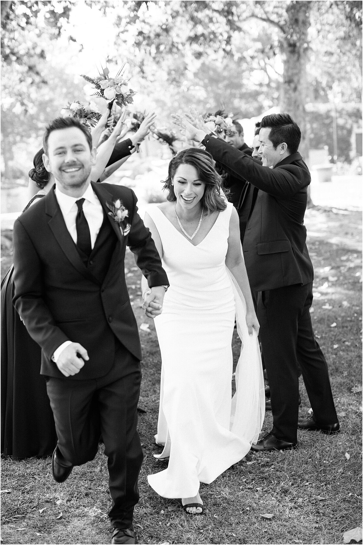 black and white image with happy couple running and laughing Carmel California