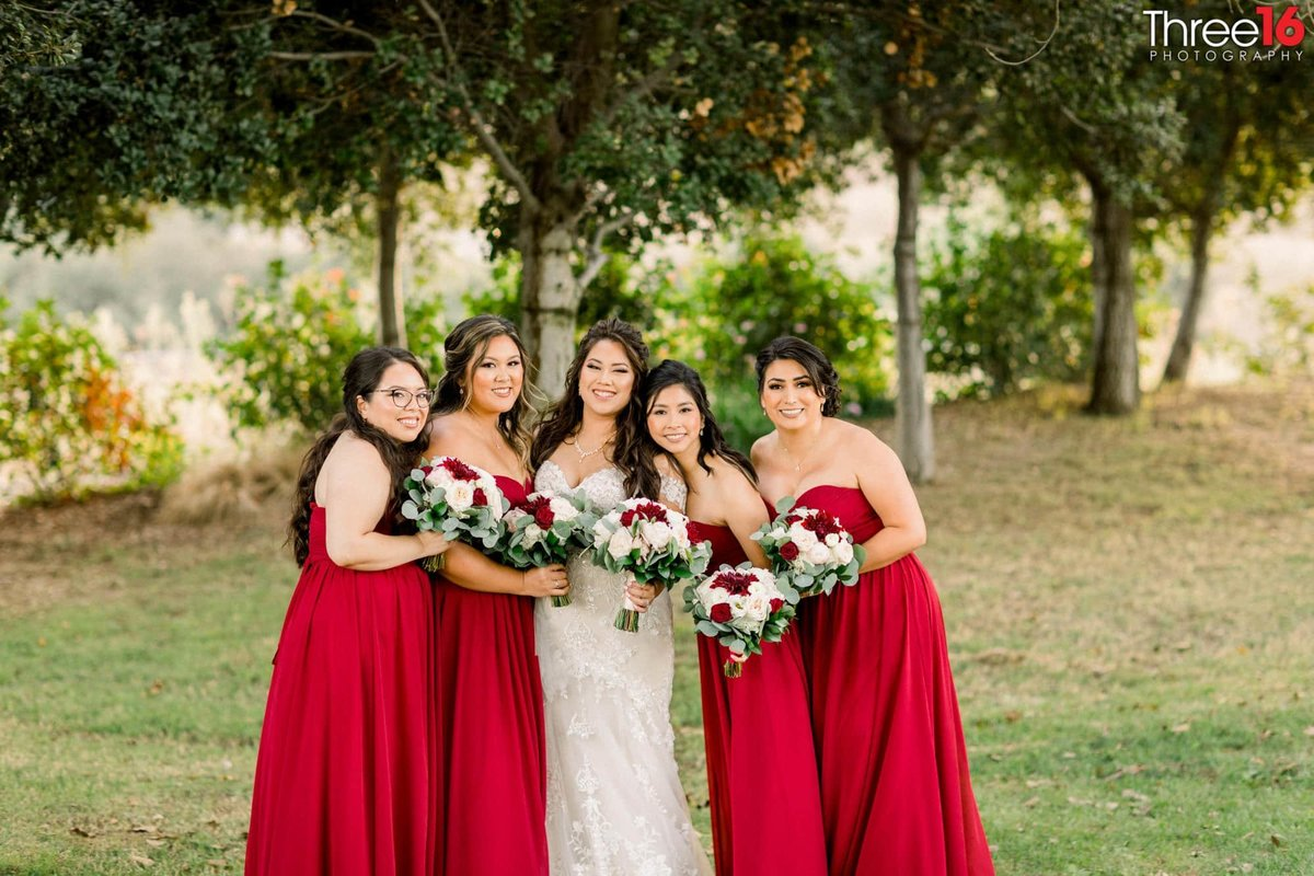 Bride and her Bridesmaids posing in the field together