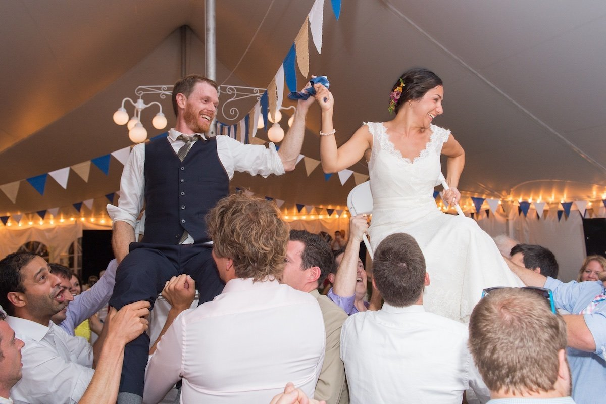 epic wedding party with bride and groom being carried on their chairs