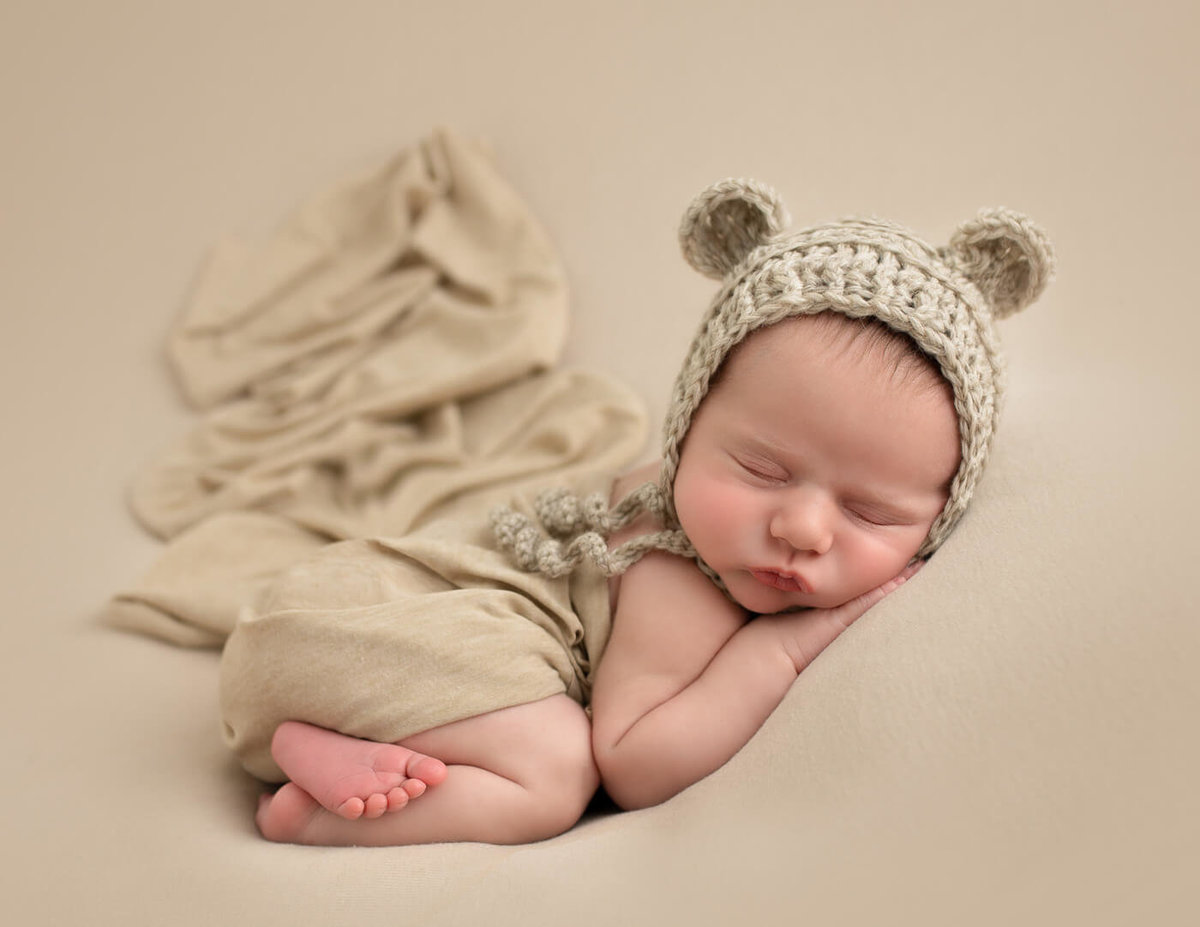 Sleepy newborn boy in bum up pose in our Rochester, NY studio.