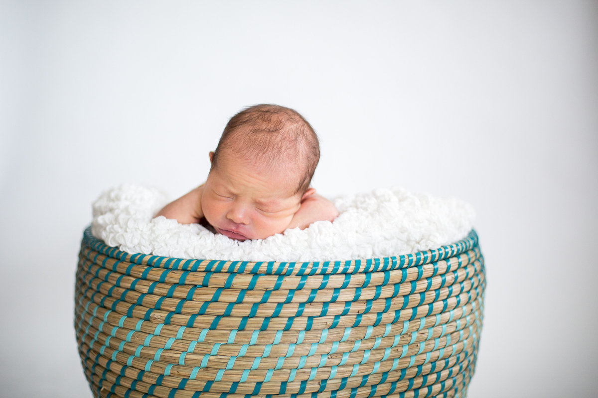 Newborn photography of infant laying in basket filled with white blanket.