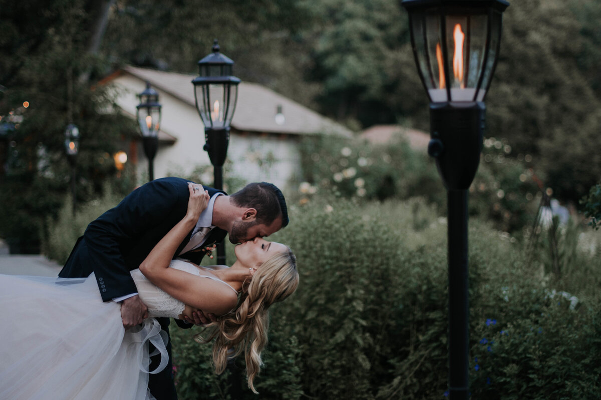 Bride-wearing-hailey-paige-wedding-dress-kissing-groom-at-romantic-cottage-with-streetlights
