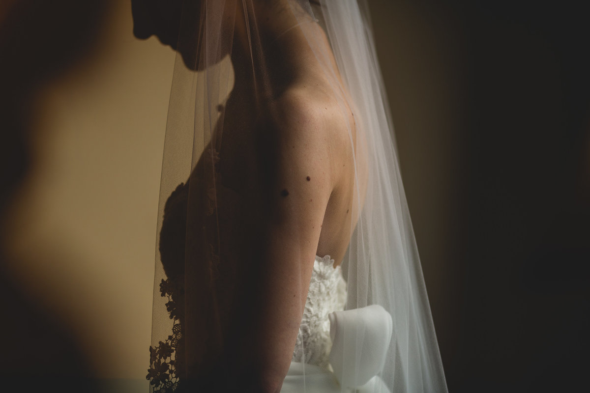 dark dramatic photo of a bride with her veil closeup