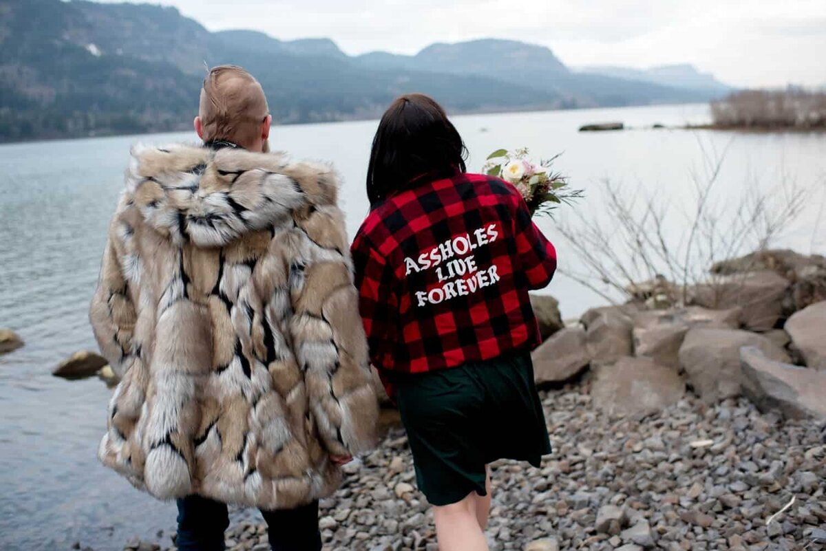 "a man in a fun faux fur coat and a woman wearing a plaid jacket that says ""assholes live forever"" hold hands while looking out at the columbia river gorge at dalton point"