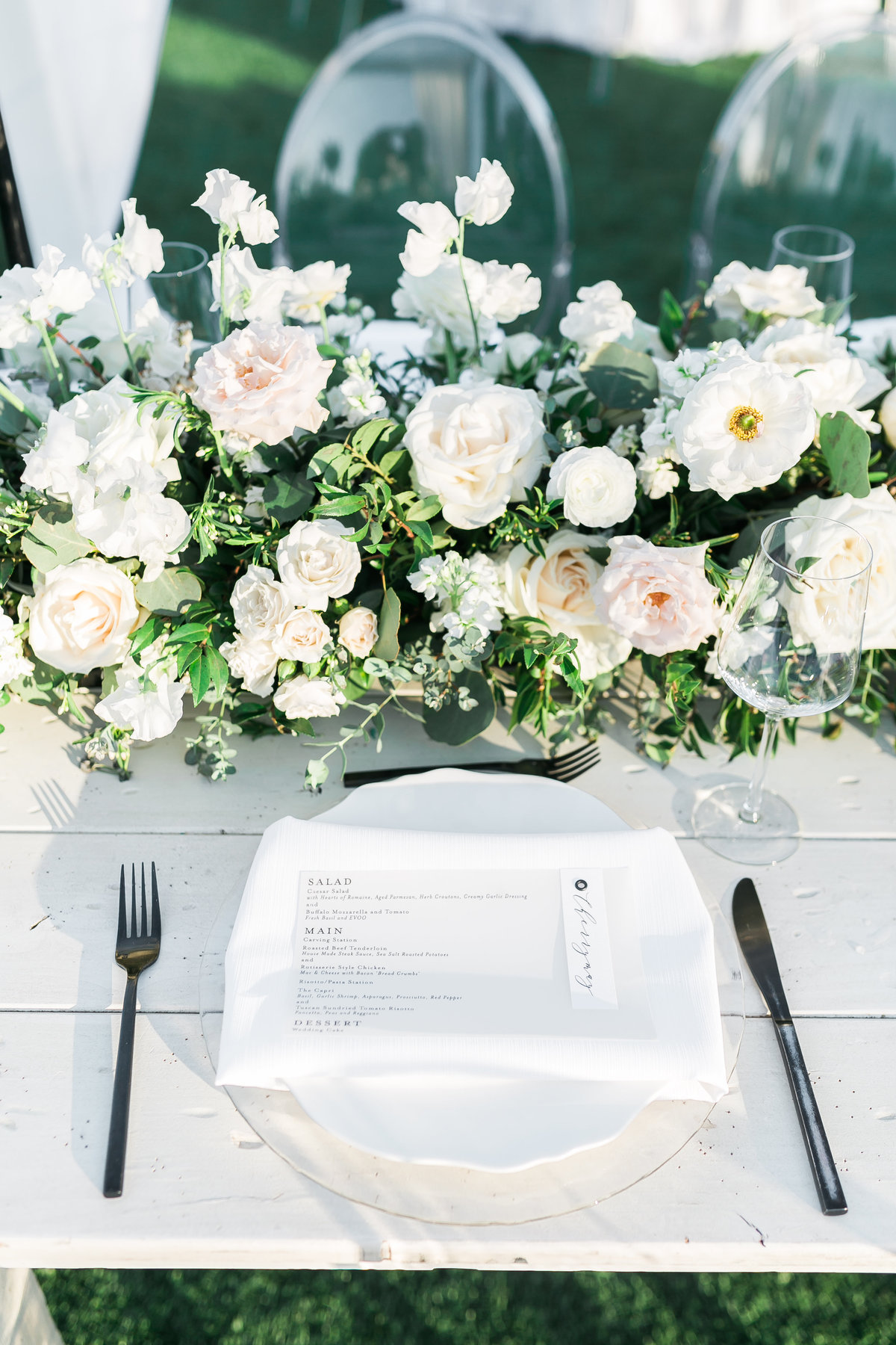 a photo of a white rustic table with black flatware and a velum horizontal menu and a lush white and greenery floral centerpiece at Green Valley Ranch Resort and Spa in Las Vegas