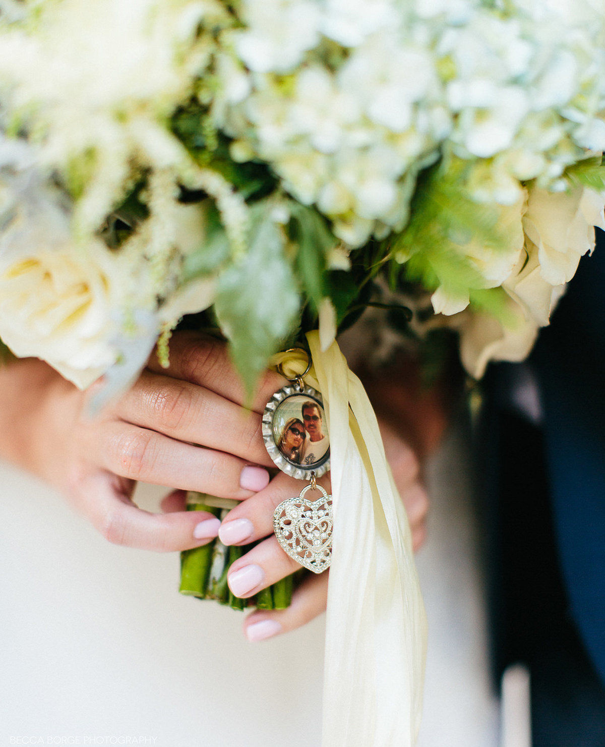 brife holding wedding boquet with a picture charm attached