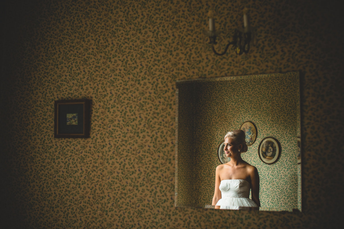 portrait of bride in mirror with vintage wallpaper. taken in window light