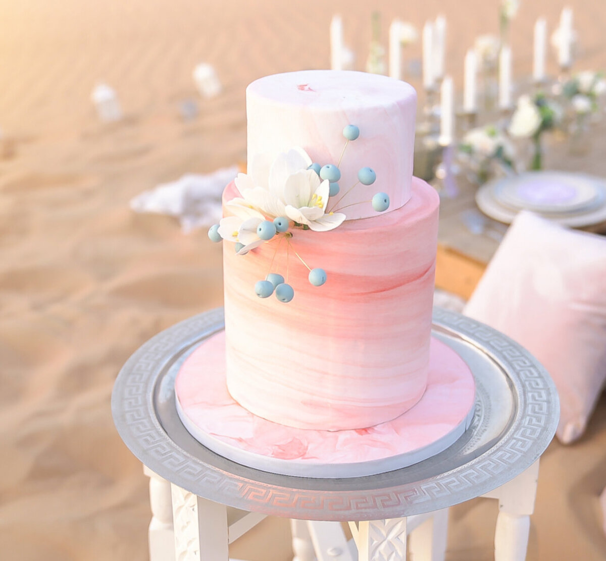 Two-tier wedding cake inspired by the movement of dunes, decorated with floral ornaments for desert elopement shoot in Dubai organized by Lovely & Planned