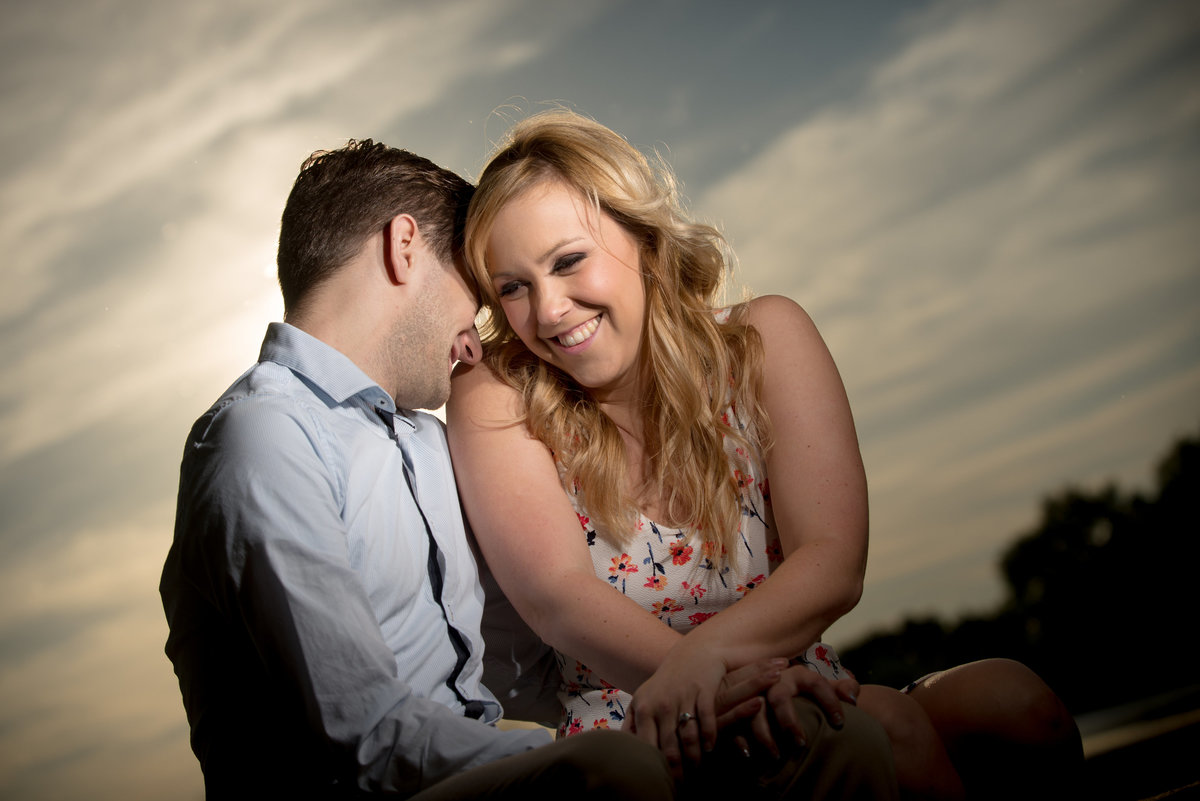 Playful giggling engagement couple at sunset