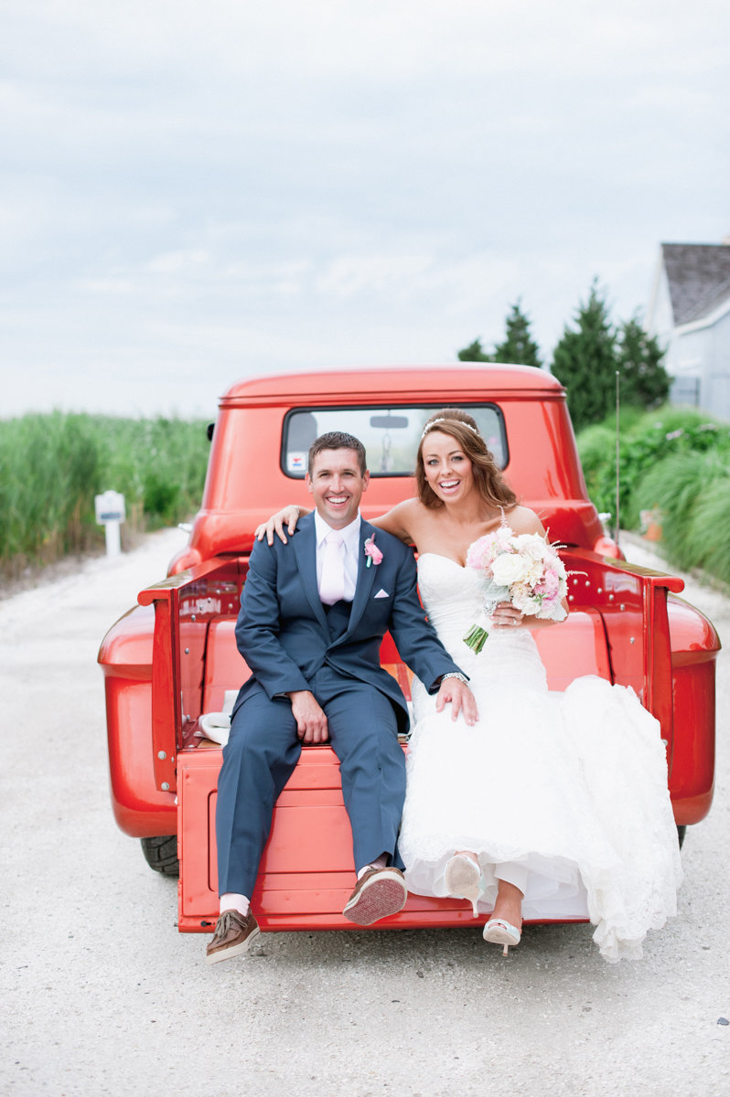 Couple just married sitting on a red Vitage red truck at bonnet Island Estate