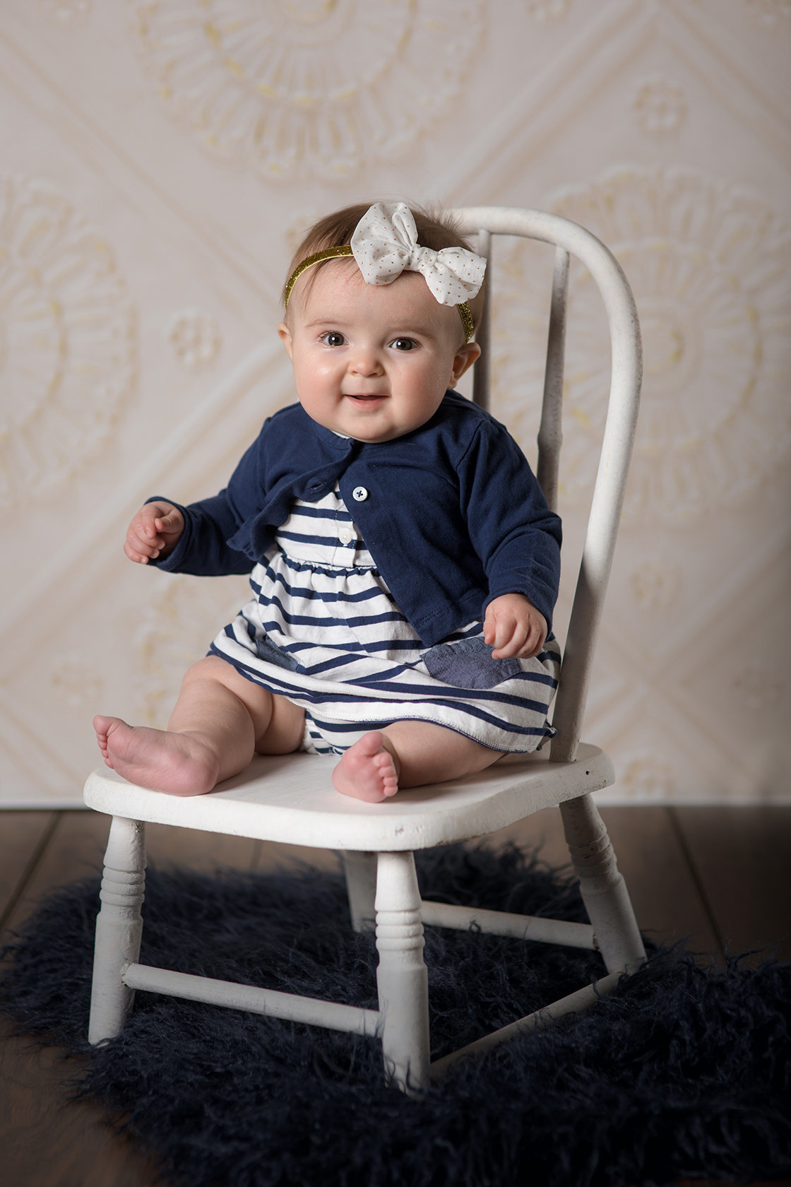 chubby baby girl sitting on chair