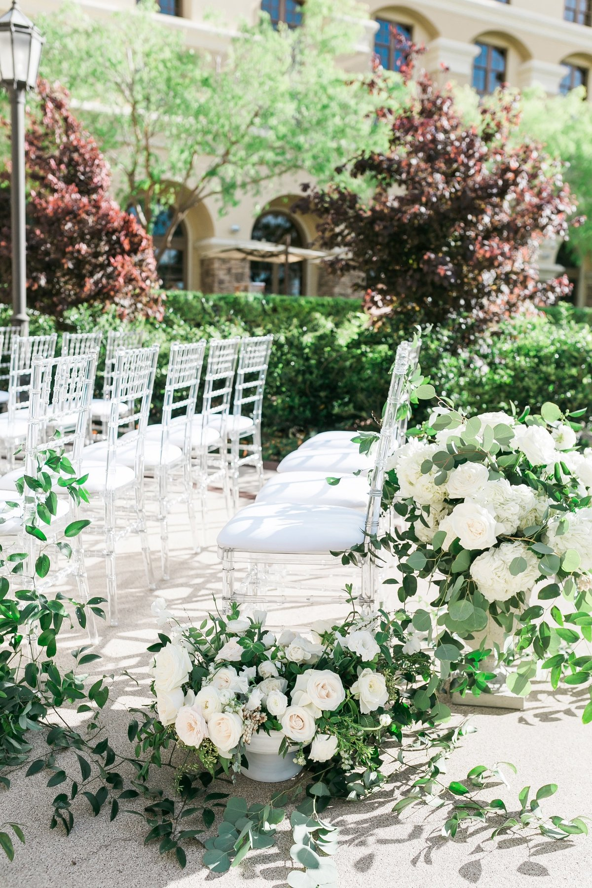 a picture of the ceremony aisle at Green Valley Ranch in Las Vegas with lush white floral aisle markers and greenery vines