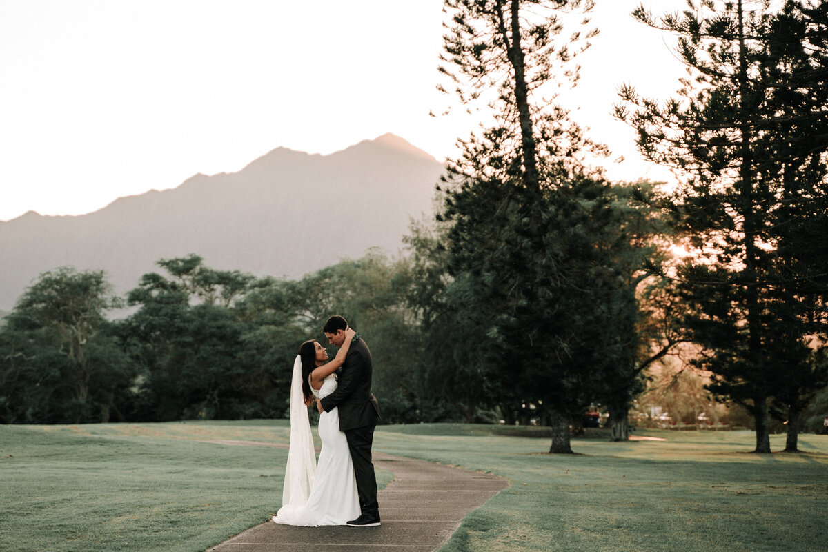 Gorgeous golf course wedding photo of bride and groom kissing at sunset