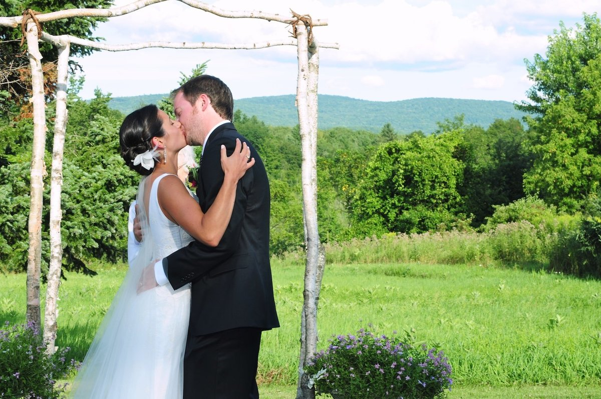first kiss as husband and wife during their outdoor summer wedding in VT