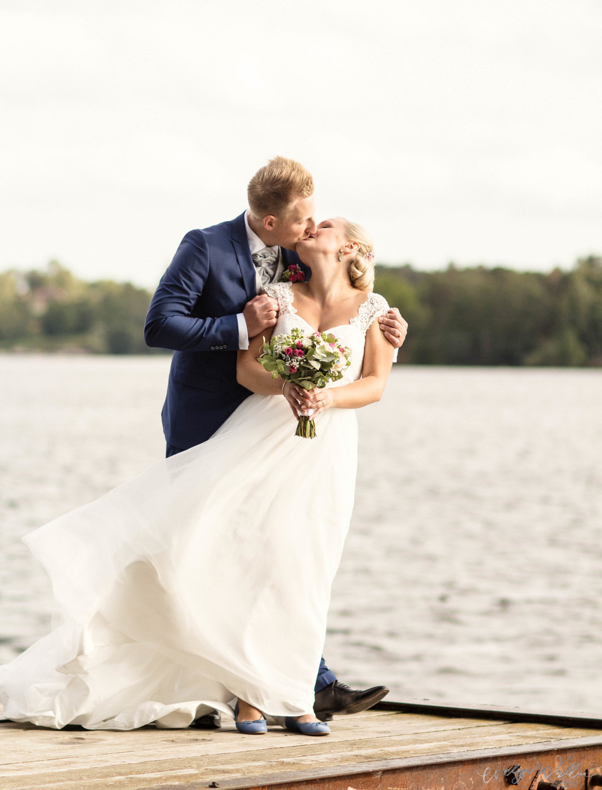 wedding couple kissing by the sea, windy portraits