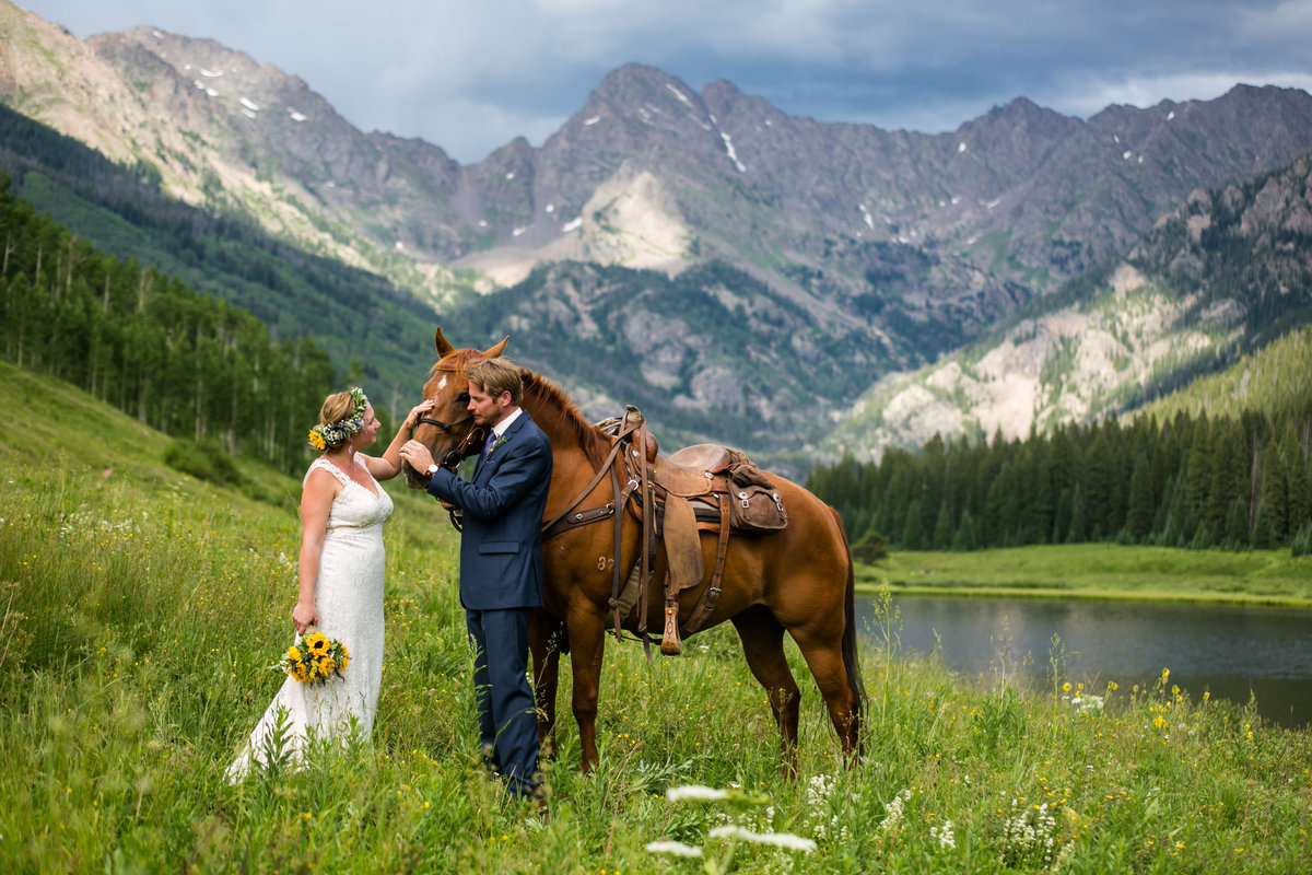 bride and groom with horse at Piney River Ranch