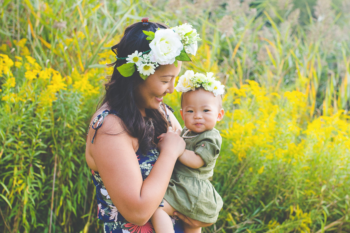 mother holding baby daughter in flowery field {Oakville Family Photographer}