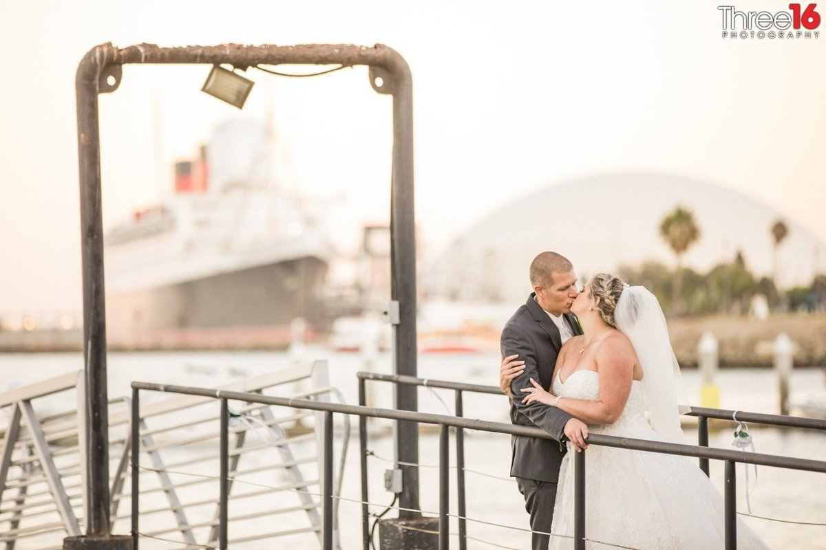 Bride and Groom share a kiss out on a dock overlooking the Long Beach Harbor