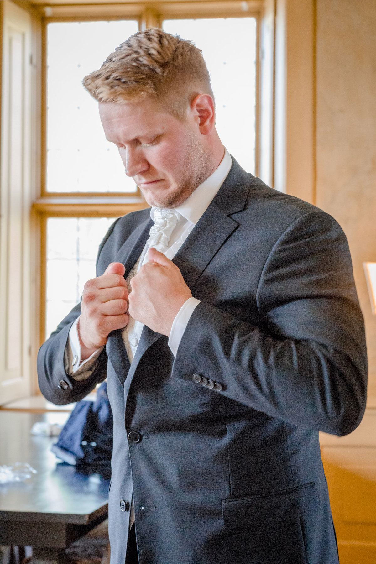 Groom putting his suit right
