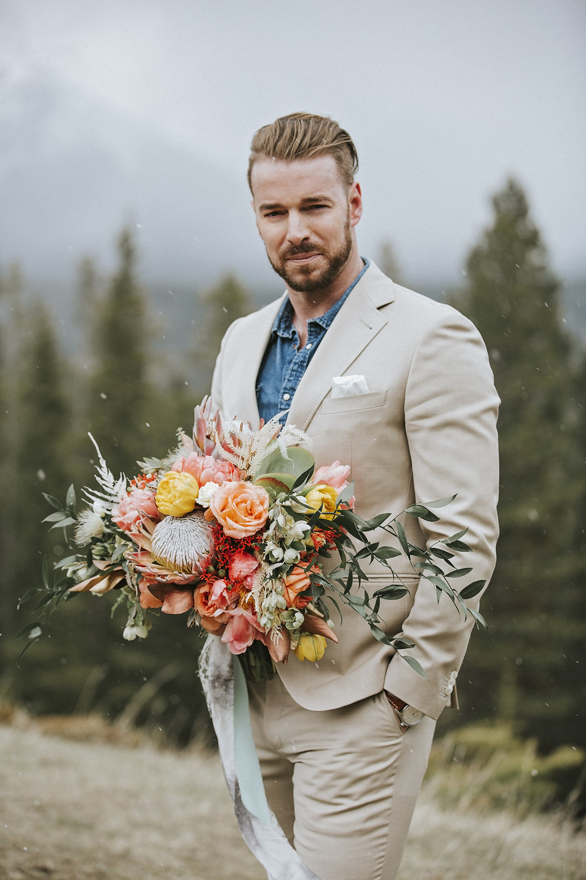Mountain wedding groom holding luxurious floral bouquet
