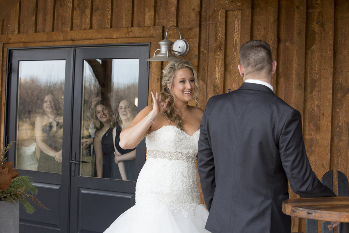 wedding party looks on while bride and groom meet at meadows barn, SD