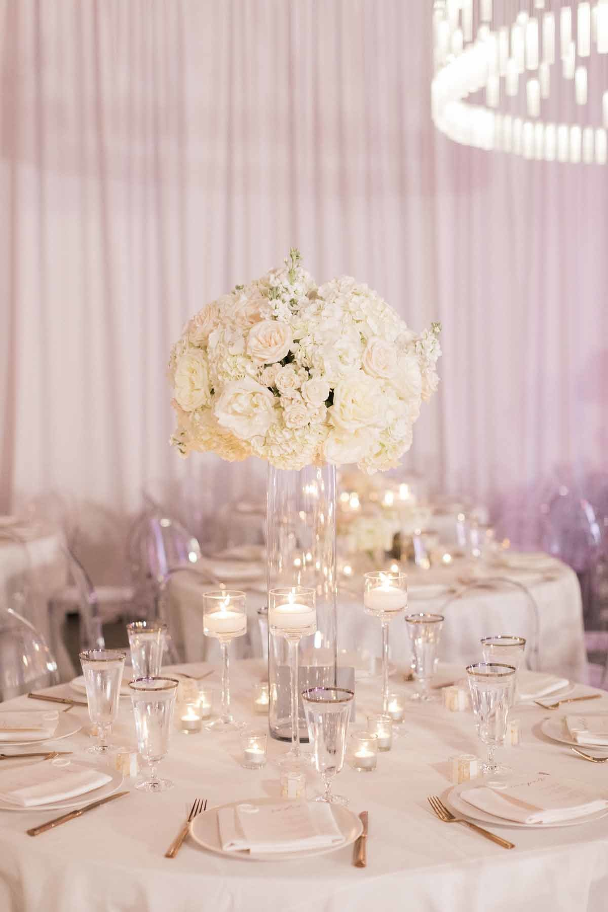 Elevated arrangement of all white roses and hydrangea seem to float in this all white space