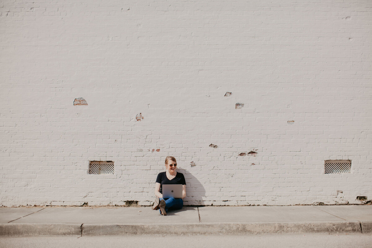 copywriter diana p. carter  sitting in front of white brick wall in charlotte, nc