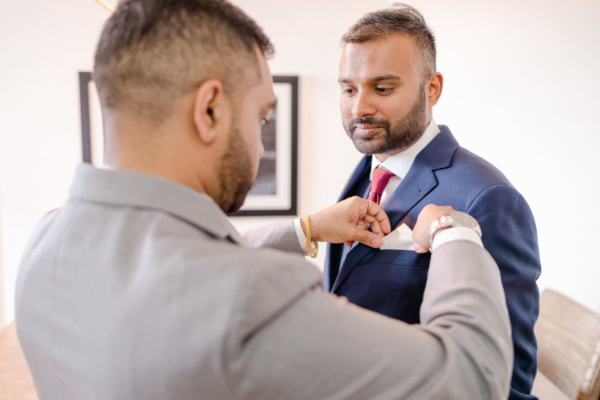 best man putting white silk handkerchief into grooms suit pocket