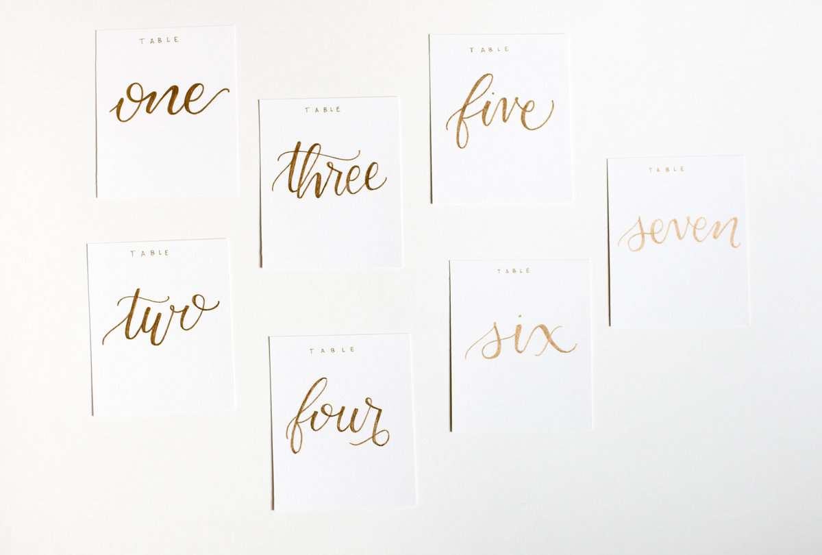 Gold hand calligraphy table numbers for weddings or events rental through Hue + FA Rentals