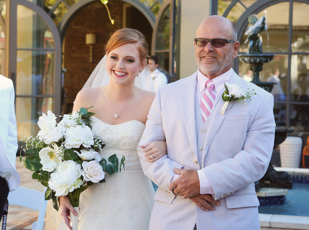 Dad walks daughter down the aisle in courtyard wedding ceremony at the Southern Hotel in Covington, Louisiana