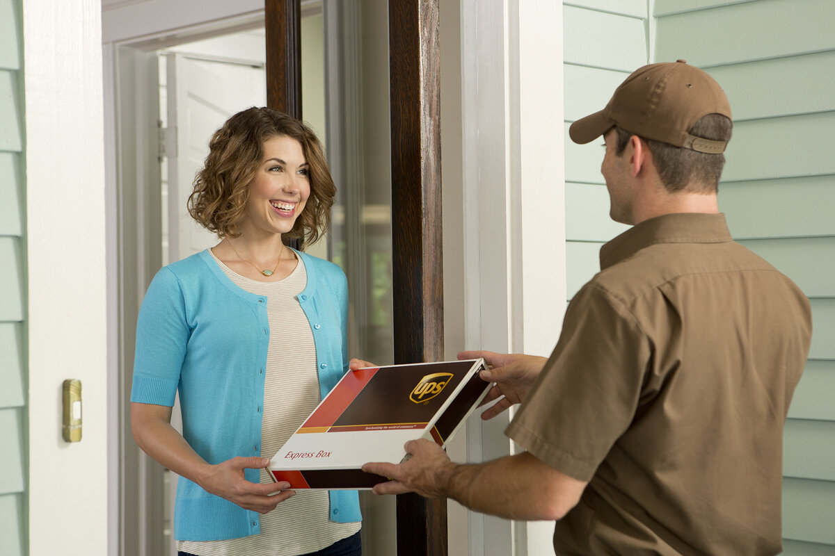 UPS my choice post man delivery man handing package to woman postman delivering package