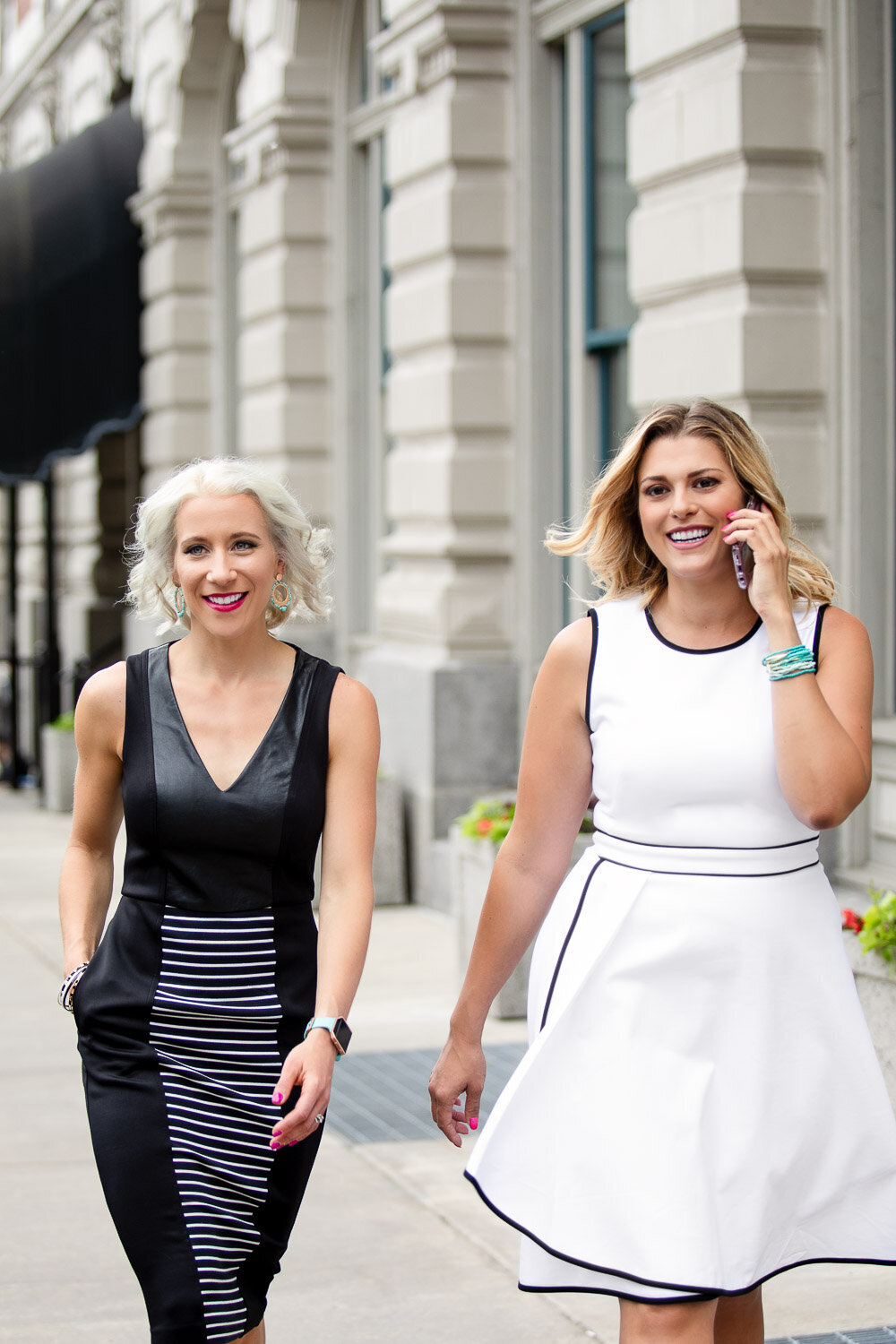 Two women colleagues walking down the street, one on the phone