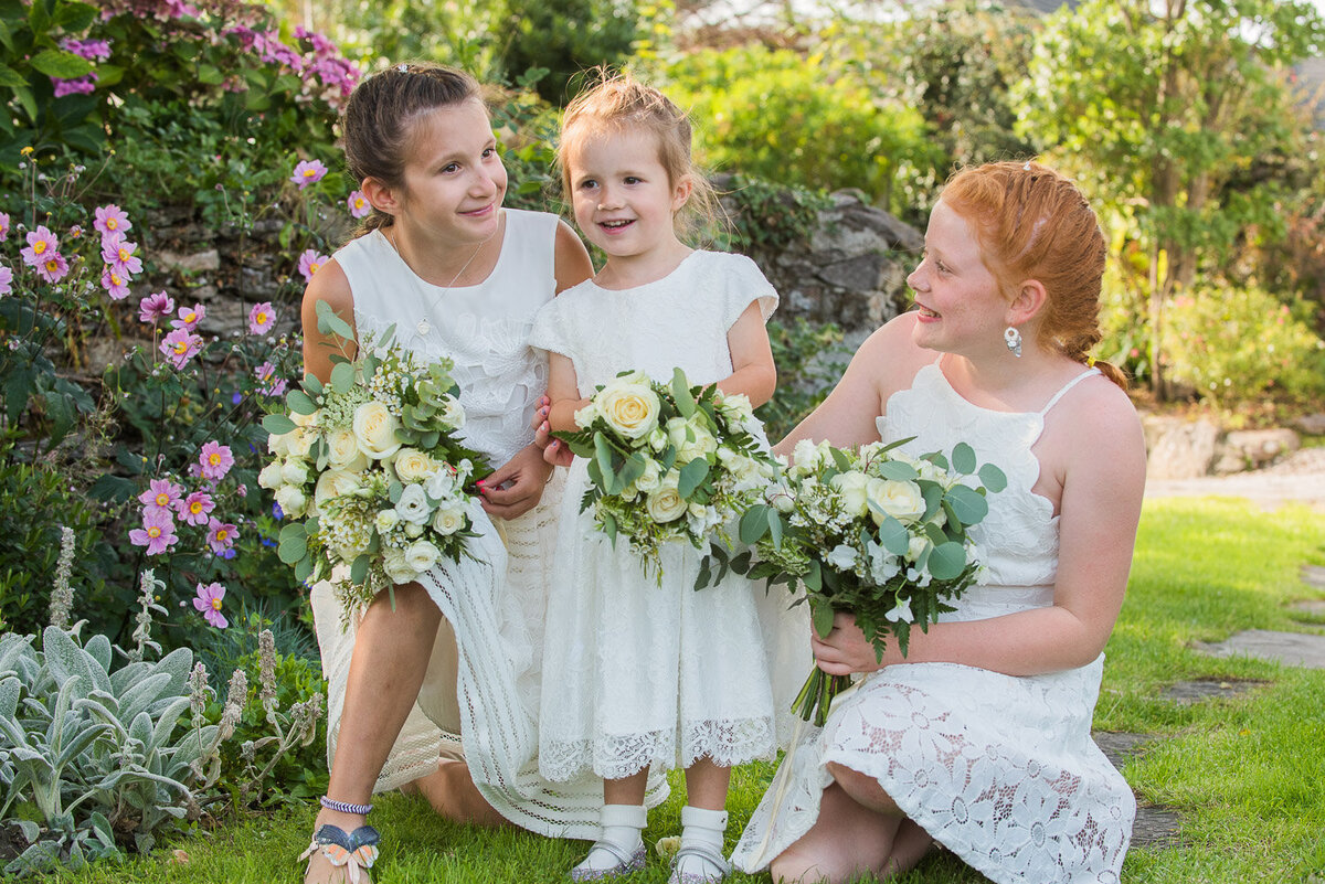 three flower girls holding white wedding bouquets in a floral garden laughing