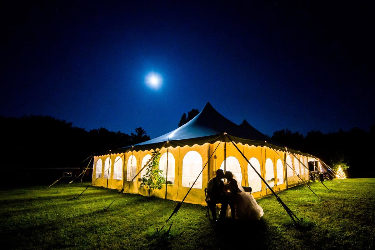 A couple kisses under the moonlight at their backyard Wisconsin wedding.