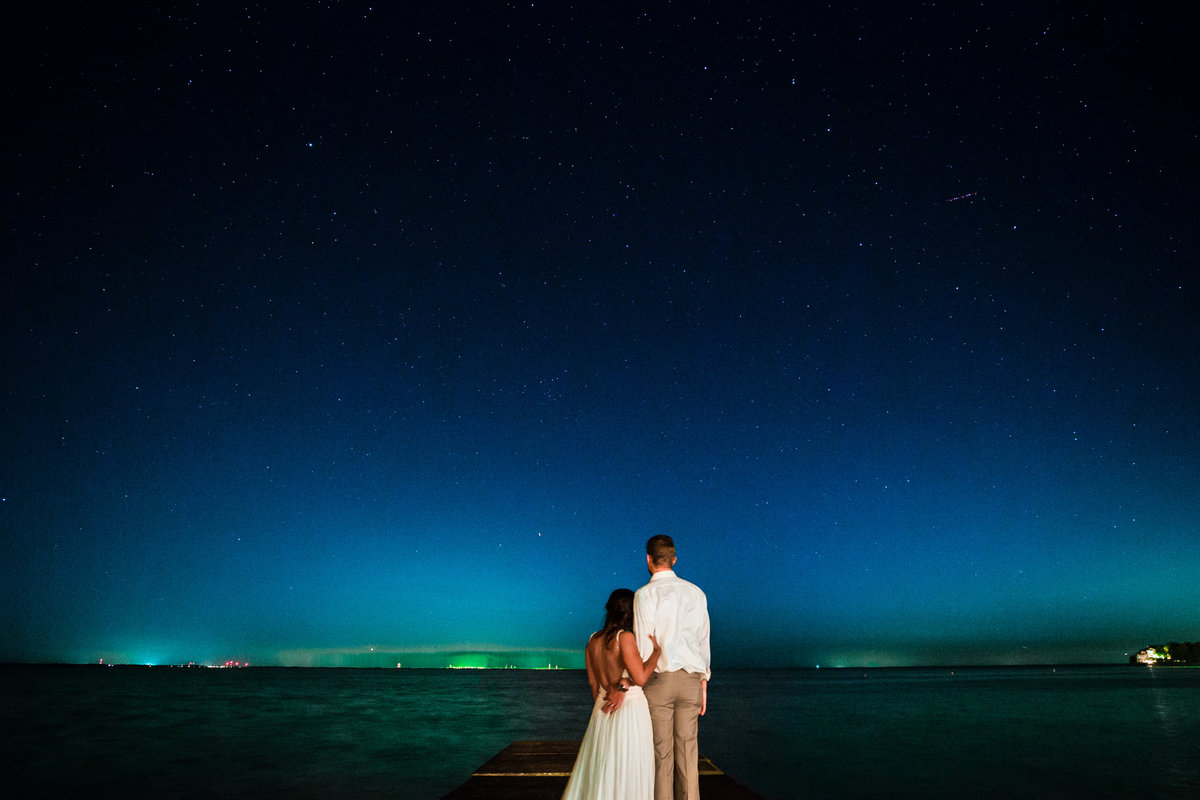 One of the top wedding photos of 2019. Taken by Adore Wedding Photography- Toledo Ohio Wedding Photographers. This photo is of a bride and groom during blue hour on the shores of lake erie