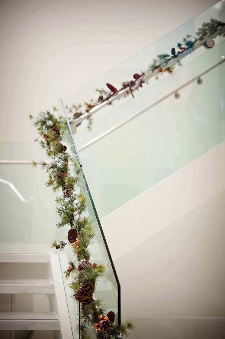 evergreen garland with acorn cones lining stairway railing