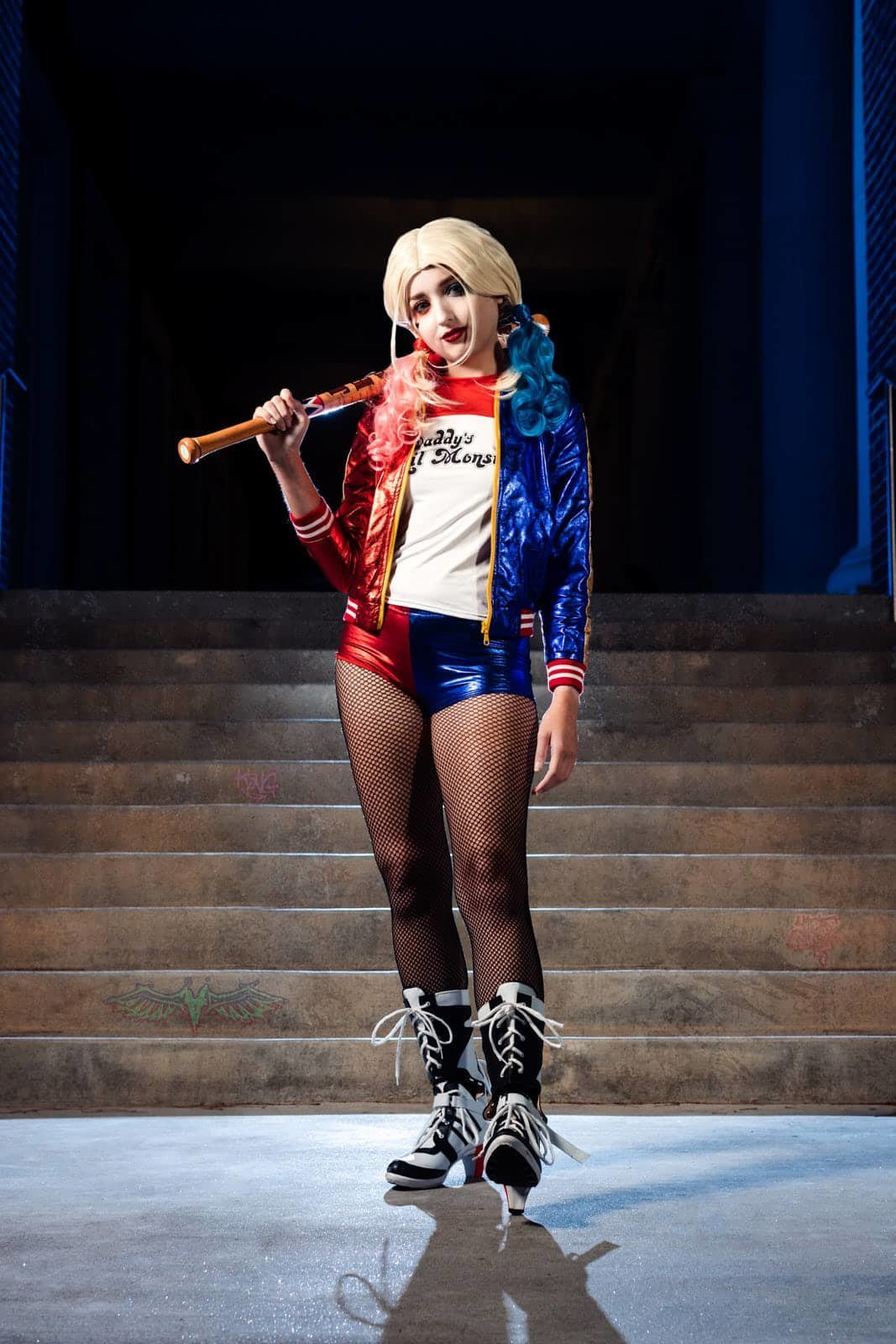 portrait of harley quinn cosplay with bat standing in front of steps Alpharetta