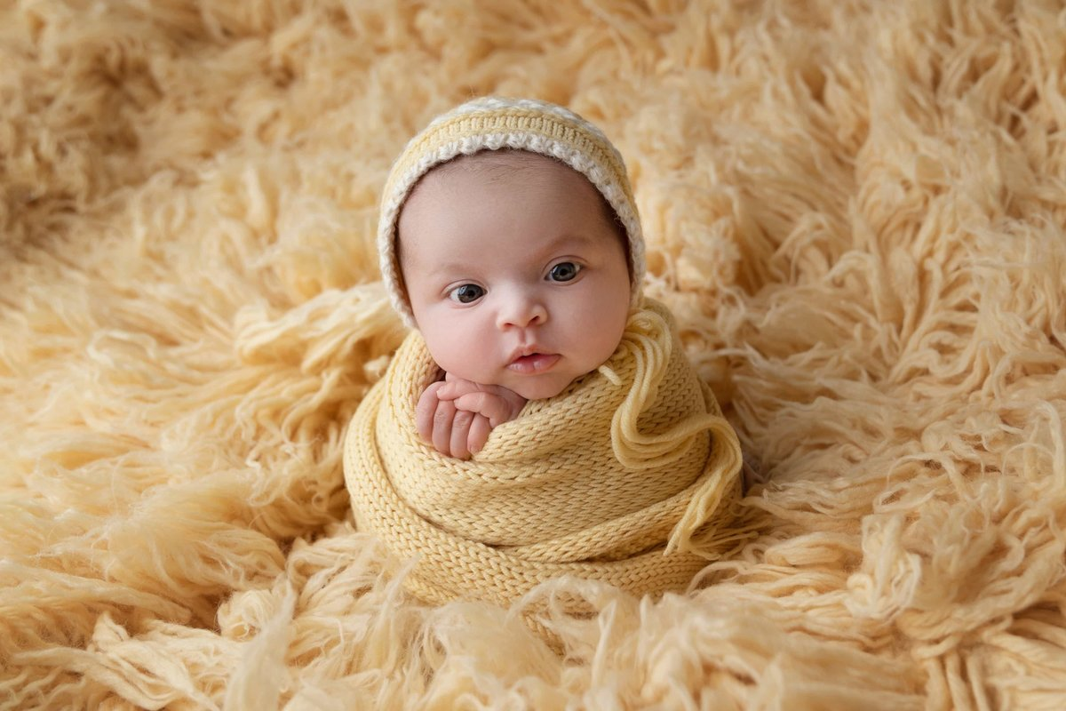 Little girl in yellow bonnet and wrap