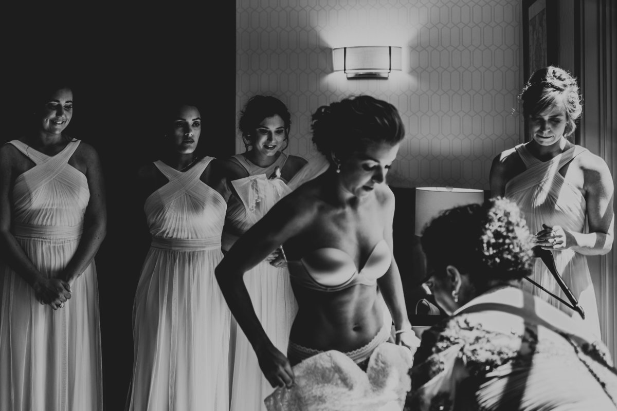 A bride slips into her gown as her bridesmaids watch on.