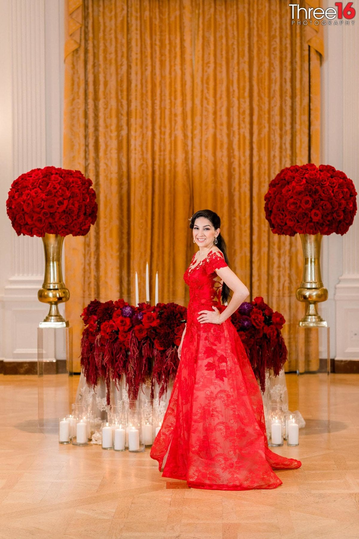 Bride dressed in a red dress stands in front of the sweetheart table
