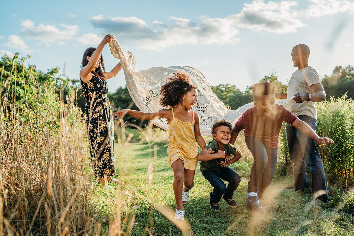 three kids hold hands and laugh while running under blanket in boston family photoshoot