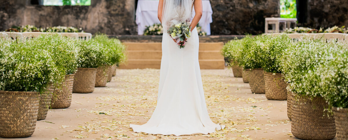 A rustic wedding aisle lined with baskets of greenery frames a bride in a white dress holding her bouquet.