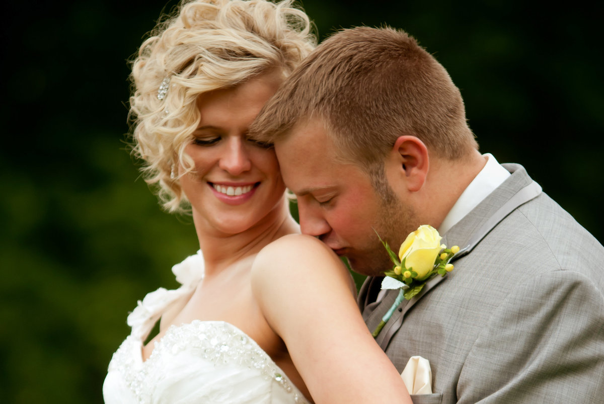 groom kissing bride's shoulder while bride is smiling