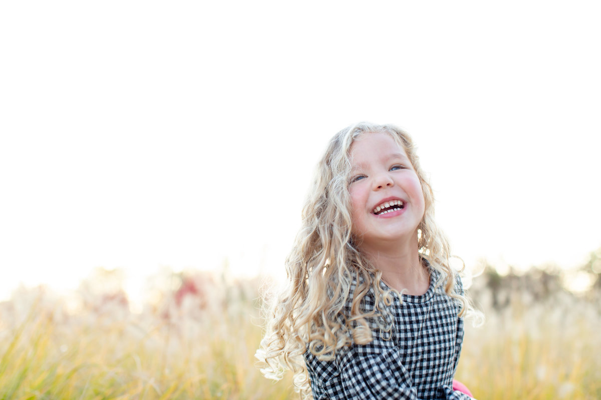 Fall Sunset Family Session girl laughing in  tall grass at Pagoda Circle in Forest Park in St. Louis by Amy Britton Photography Photographer  in St. Louis