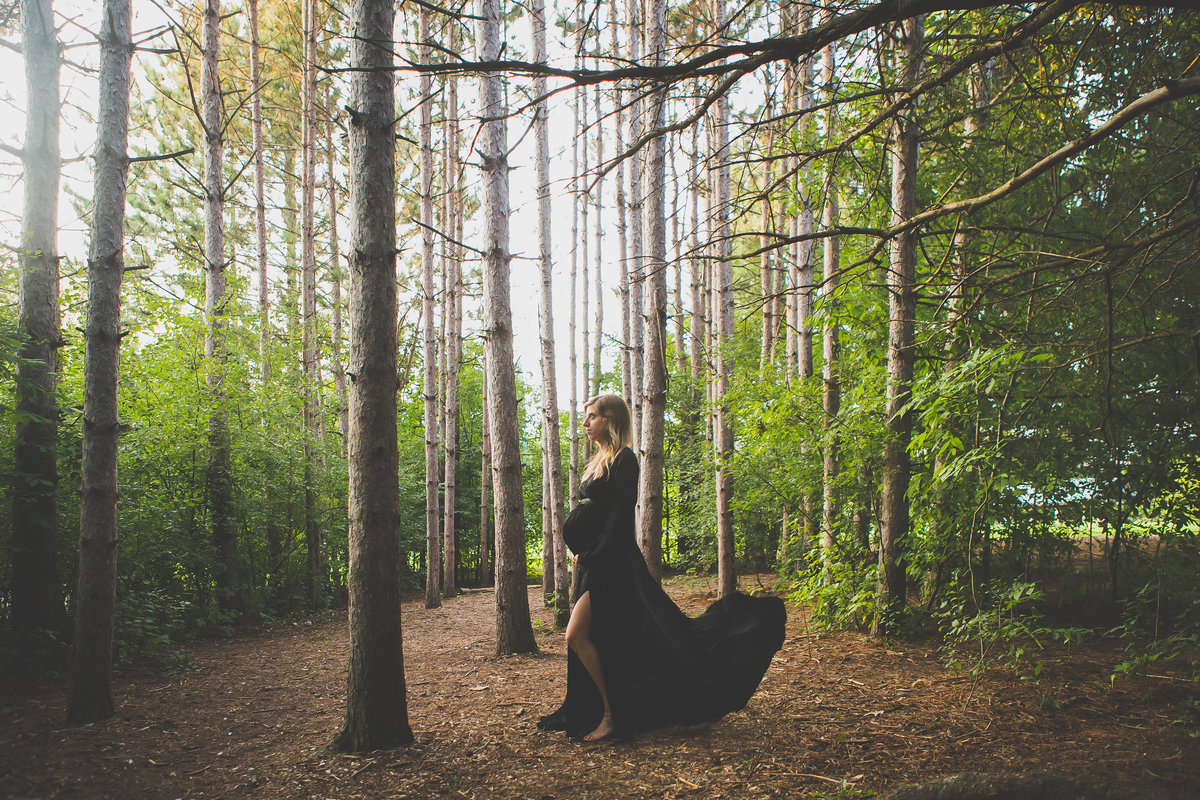 Pregnant woman in forest with black dress flowing in the wind {Milton Maternity Photographer}