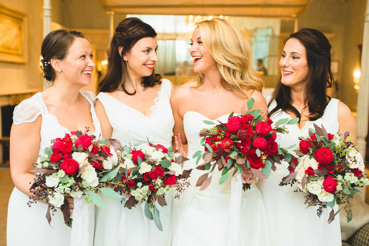 bridesmaids and bride at babington house holding red roses and laughing in a natural pose