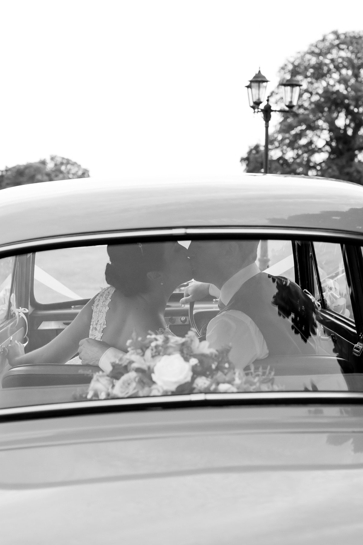 kissing in the wedding car at upton barn