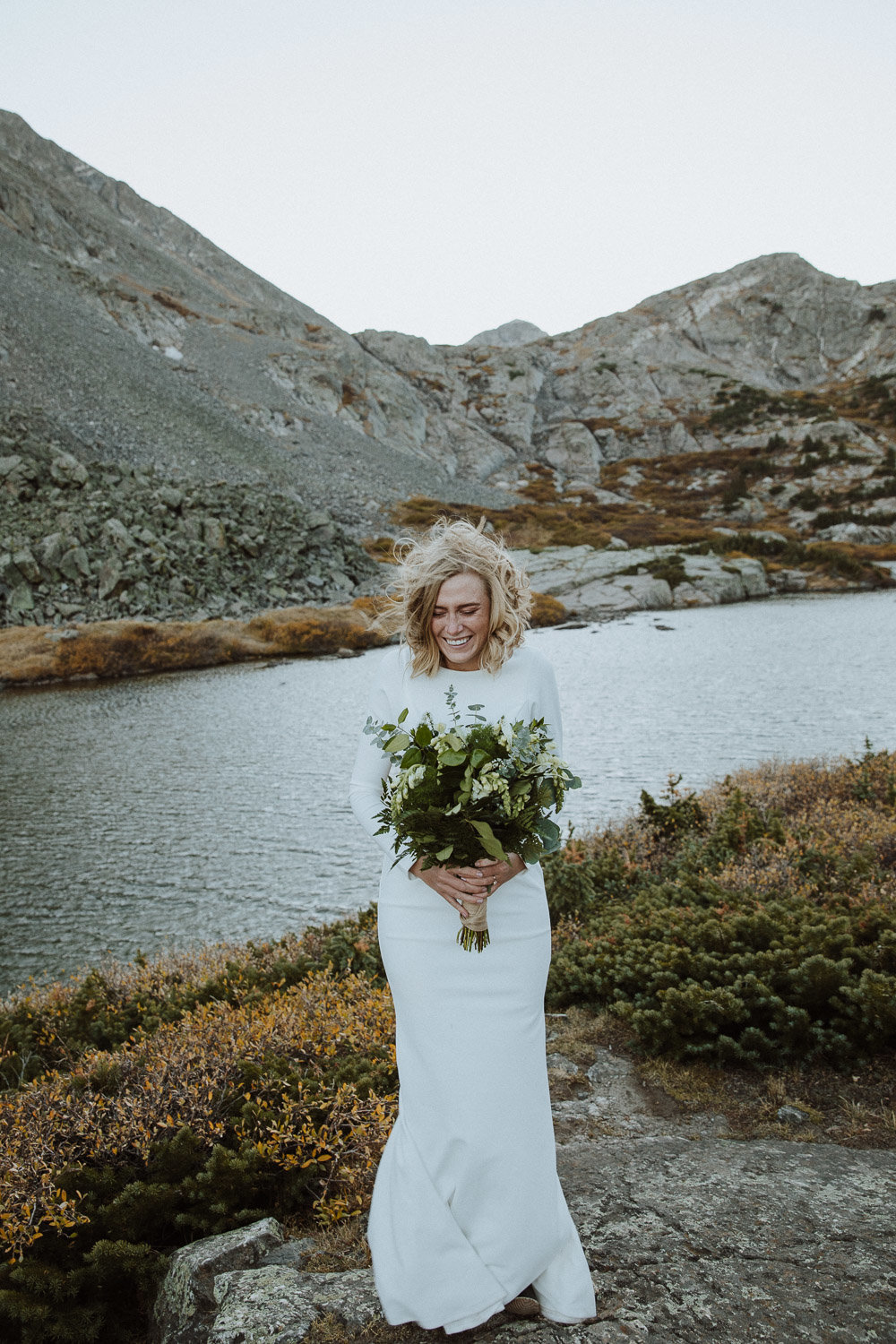 A photo of a bride standing in front of a mountain river holding a large white wedding bouquet, looking down and smiling