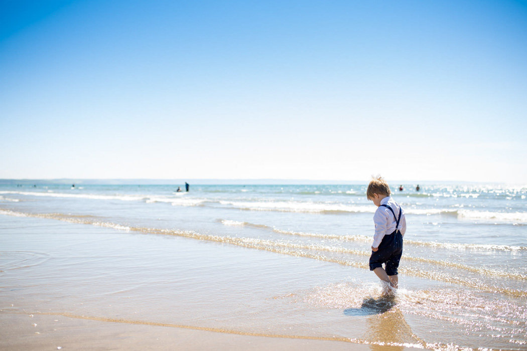 Page boy walking in the sea at Woolacombe Bay Devon