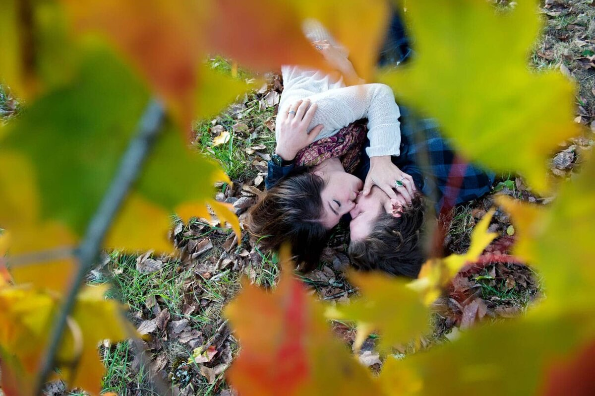 a man and woman lay on the ground underneath a tree full of fall colored leaves